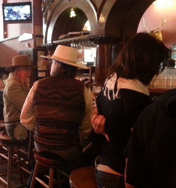 a couple of cowboy types enjoy a beer at the Palace.